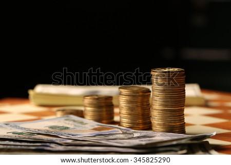 Money on a chessboard, black background - stock photo