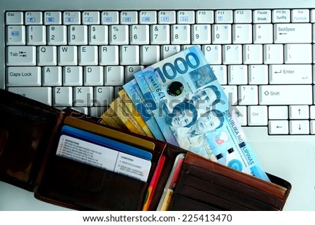 Money on a Computer laptop Photo of a computer laptop with a bunch of money on top - stock photo