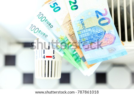 Money on a radiator symbolizes the expensive heating costs.