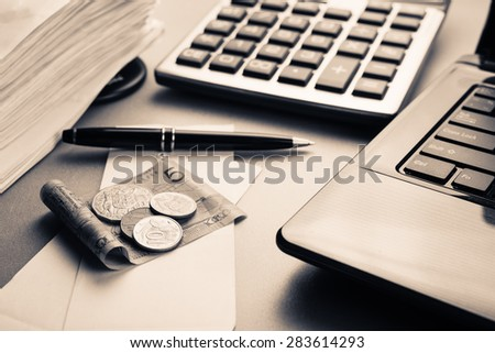 Money on bills with laptop and calculator