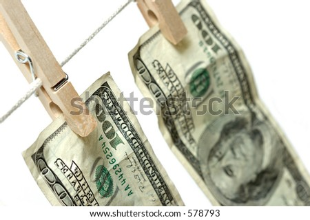 money on clothesline - money laundering. closeup with limited depth of field, focus on rear 100 of first bill