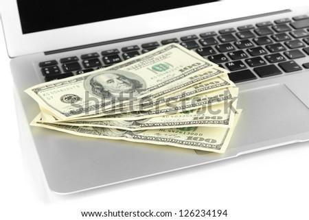Money on laptop isolated on white - stock photo