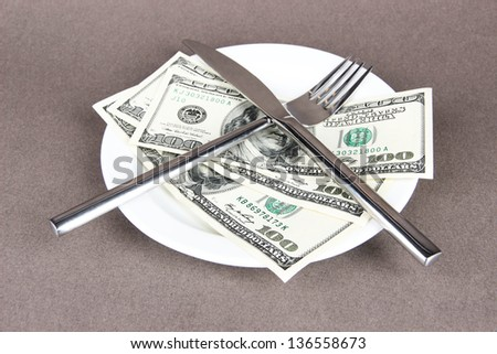 Money on plate on grey background