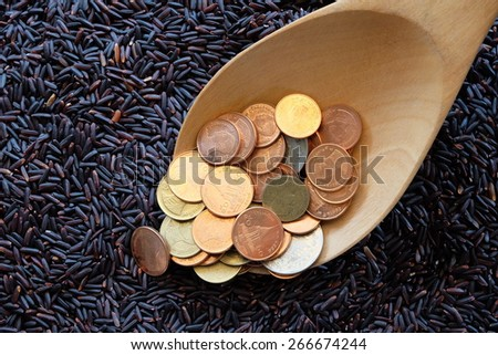money on spoon and purple rice background with business concept - stock photo