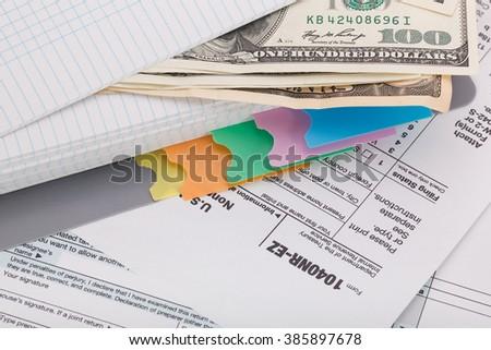 Money on tax form background - stock photo