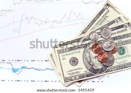 money on top of a stocks charts. - stock photo