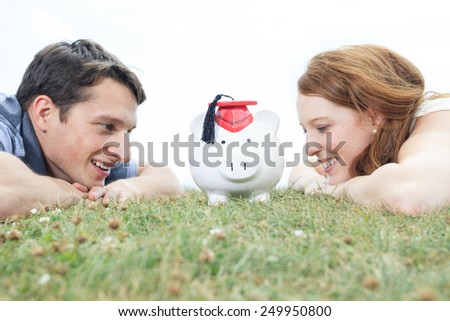 money, outside, finance and relationships concept - smiling couple with piggybank - stock photo