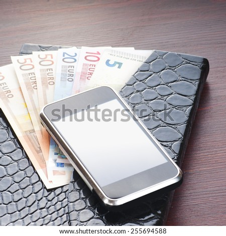 money, phone and notebook on the table - stock photo