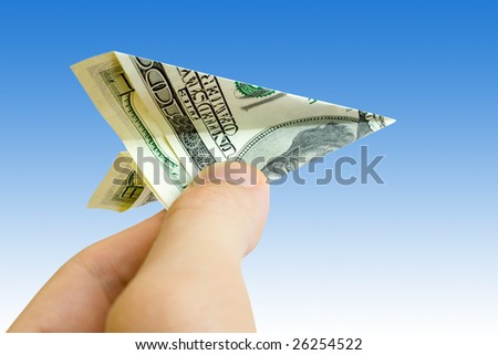 money plane in fingers over blue background - stock photo