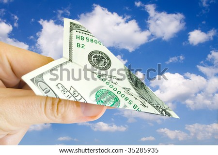 money plane in fingers over sky with clouds - stock photo