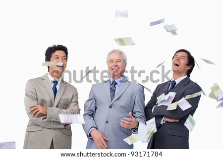 Money raining down on businessteam against a white background