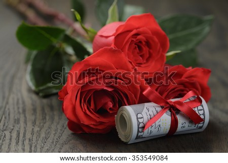 money roll with rose flower on wooden table - stock photo