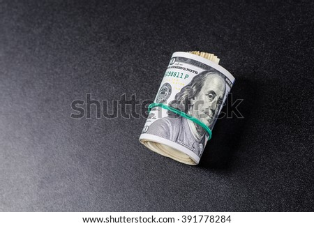 Money roll with US dollars. Selective focus. - stock photo