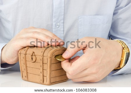 Money savings concept. Male hand putting coin into a money-box. - stock photo