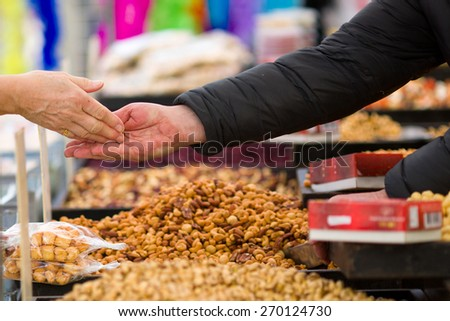 Money transaction in a tradtional way on a weekly market in Breda, the Netherlands, where a customer is handing over cash money to the salesman - stock photo