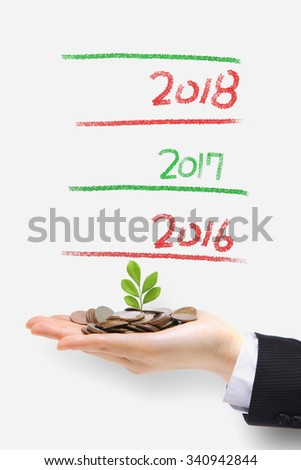 money tree grow up in 2016 new year - green plant sprouting from hand with money,concept for business and new year - stock photo
