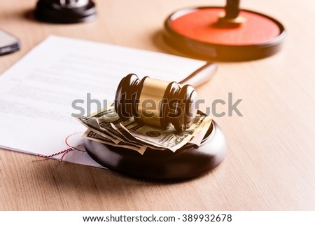 Money under the judge's gavel. Notary public stamper and notary act in the background. Bribe, corruption concept.