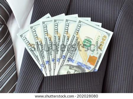 Money - United States dollar (or USD) banknotes in suit pocket - stock photo