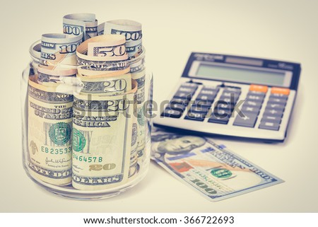 Money, US dollar bills, with calculator on white table - financial and accounting concepts, vintage tone