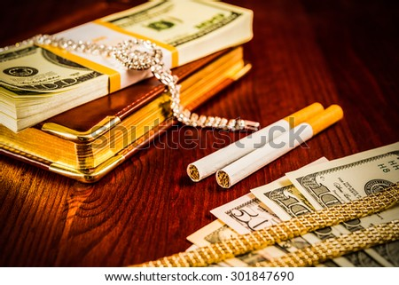 Money with a leather diary and cigarettes with jewellery on a mahogany table. Image vignetting and hard tones