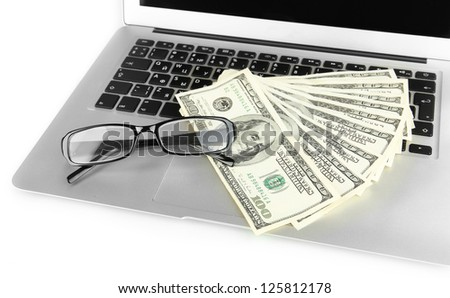 Money with glasses on laptop isolated on white - stock photo