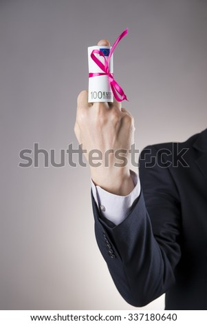 Money with ribbon in male hand on a gray background. Business concept - stock photo