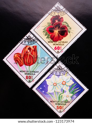 MONGOLIA - CIRCA 1983: A stamp printed in Mongolia shows three kinds of colorful flowers, circa 1983. - stock photo