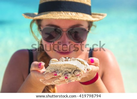 Monica is holding crab next to her face and smiling like a chlid