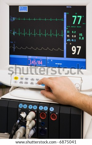 monitor with doctor's hand in intensive care unit - stock photo