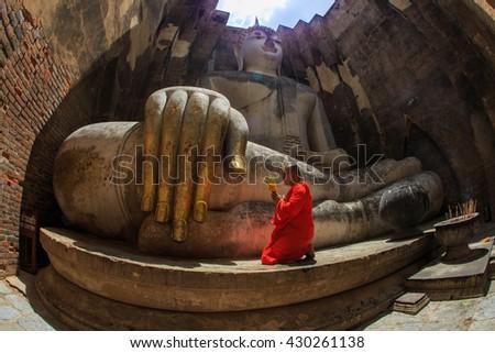 Monk ,Buddha ,Monk with Buddha in Wat Si Chum at Sukhothai historical Park,Thailand-28 may 2016. - stock photo