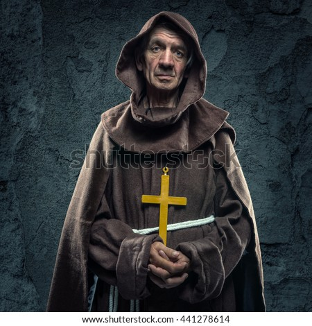 Monk holding a wooden cross in front of the old walls - stock photo