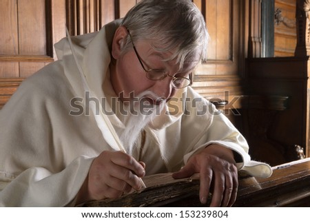 Monk with beard writing with a feather in an old book - stock photo