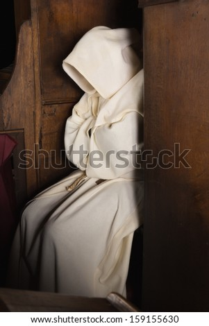 Monk with hood sitting in a wooden corner of a medieval church