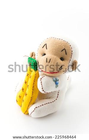 monkey doll with banana on white background - stock photo