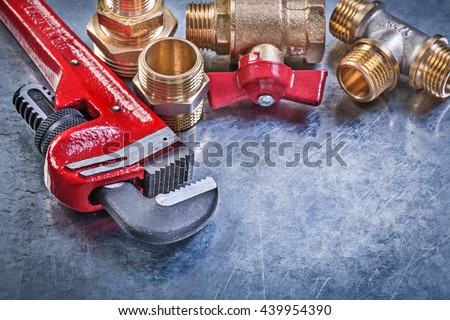 Monkey wrench brass plumbing fittings gate valve on metallic background.