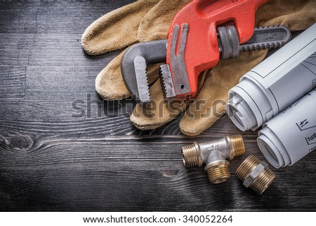 Monkey wrench copper plumbing fixtures safety gloves blueprint rolls. - stock photo