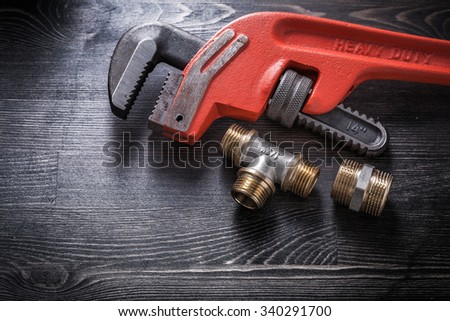 Monkey wrench plumbing fittings on wooden board construction concept. - stock photo