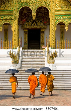 monks going to a temple, Luang Prabang, Laos - stock photo