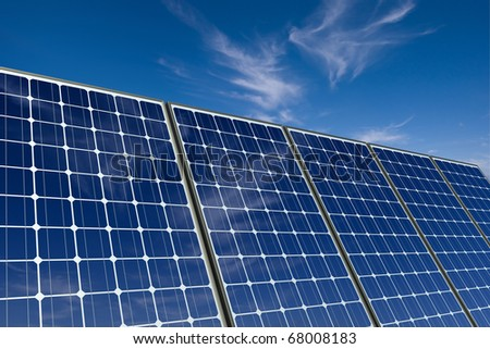 mono-crystalline solar panels against a blue sky - stock photo