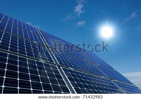 mono-crystalline solar panels against a sunny sky - stock photo