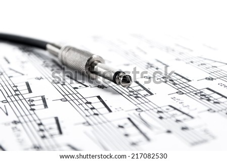 Mono guitar jack over music  - stock photo