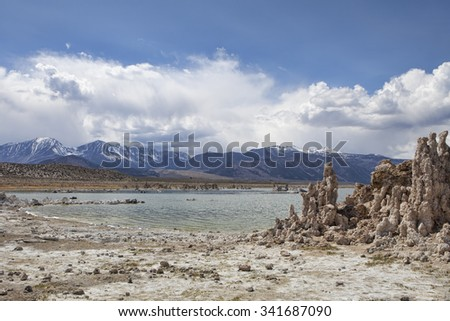 Mono Lake in California with tufa towers and clouds building over the mountains. - stock photo