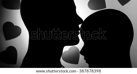 Monochromatic mannequin couple kiss against black hearts background