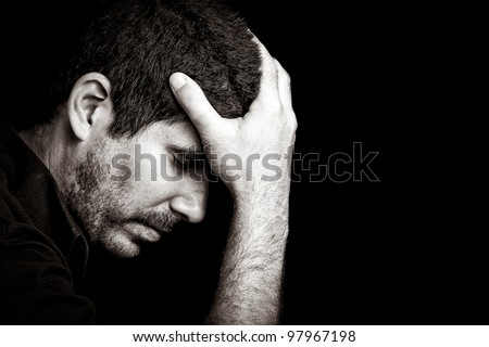 Monochromatic portrait of a worried or depressed young hispanic man isolated on black - stock photo