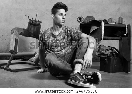 Monochromatic portrait of handsome young man against grey background - stock photo