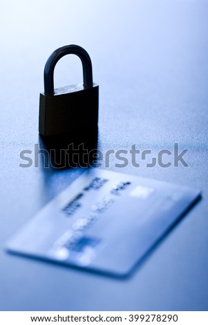 Monochromatic shallow depth of field shot featuring silhouette of an locked padlock close to a credit card - concept of security - stock photo