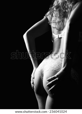 Monochrome back of a woman in whites panties and bra in front of black background  - stock photo