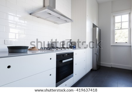 Monochrome clean white kitchen bench top and cupboards with appliances - stock photo