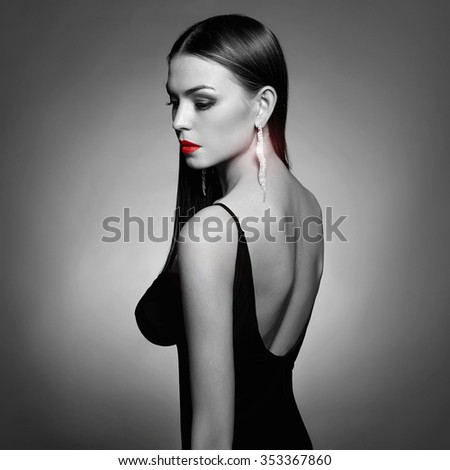 Monochrome fashion photo of glamor beautiful young woman in sexy dress with open back wearing jewelry.beauty brunette girl - stock photo