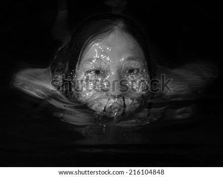 Monochrome image of a woman floating in water on a black background - stock photo